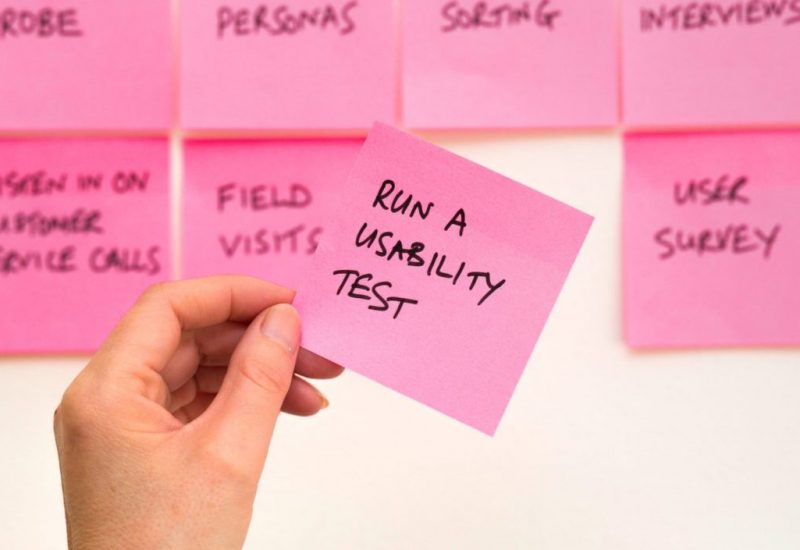 Person holding pink sticky notes with research tasks